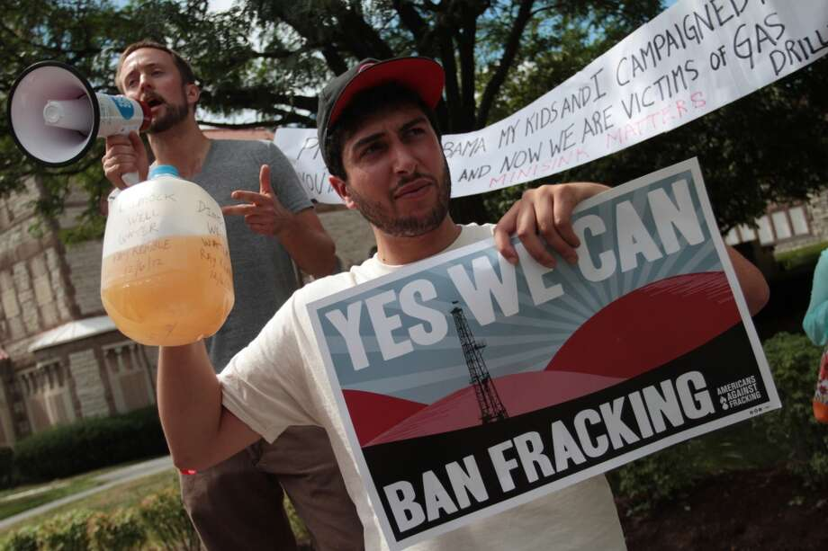 Matt Smith, left, and Alex Lotorto protest against fracking outside of Lackawanna College before President Barack Obama arrives in Scranton, Pa., on Friday, Aug 23, 2013. (AP Photo /The Times-Tribune, Jake Danna Stevens) Photo: Associated Press