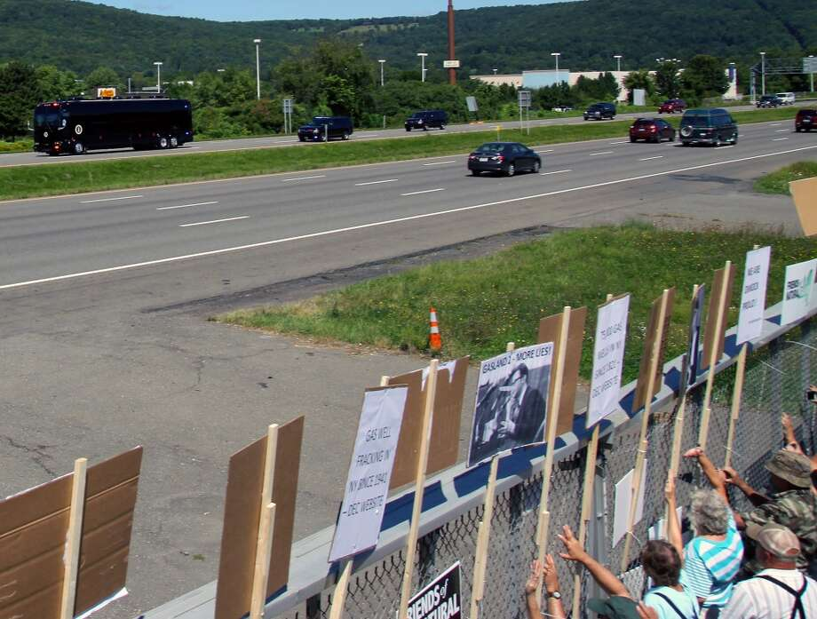 Demonstrators rally as the presidential motorcade passes by Otsiningo Park on Friday, Aug. 23, 2013, in Binghamton, N.Y. Supporters and opponents of fracking lined the route being taken Friday by visiting President Barack Obama, shouting messages for him while trying to pressure Gov. Andrew Cuomo as he weighs whether to allow the practice in New York. (AP Photo/Press & Sun-Bulletin, Jeff Miller) Photo: Associated Press