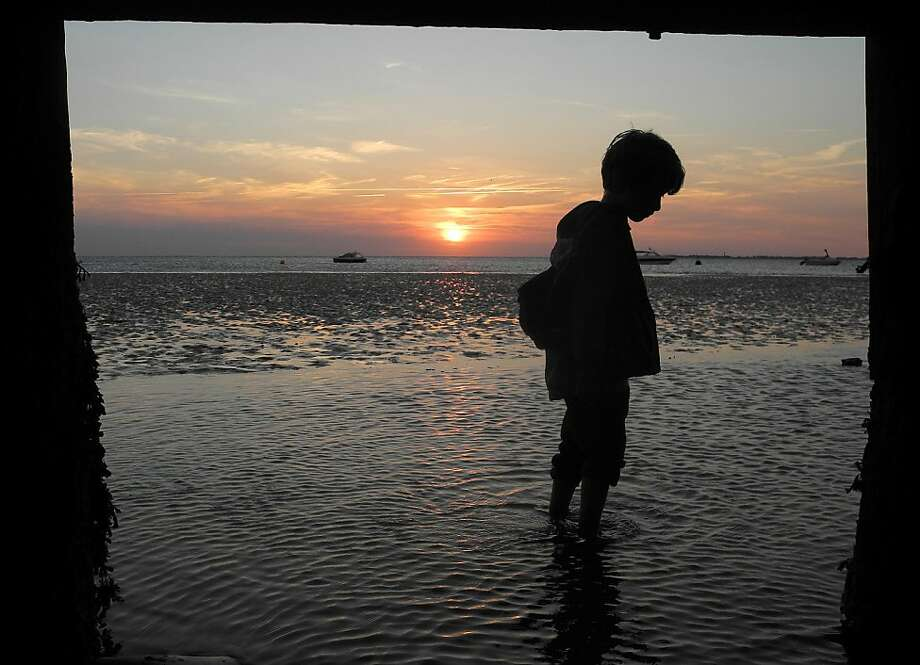 End of summer: A boy walks in ankle-deep water along a mudflat near Utersum on the German island of Foehr, North Sea. Photo: Federico Gambarini, Associated Press