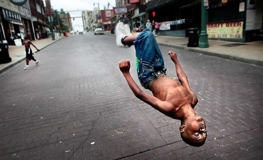 Head over heels on Beale: Ten-year-old Markese Jones flips down Memphis' famed Beale Street as fellow 