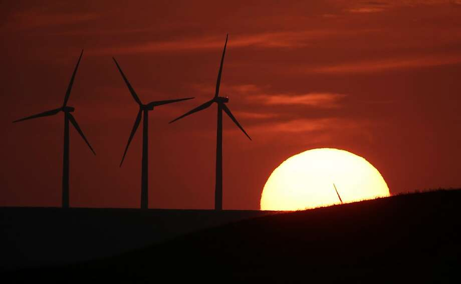 Harvesting the breeze: Elk River Wind Farm turbines are silhouetted by the setting sun 