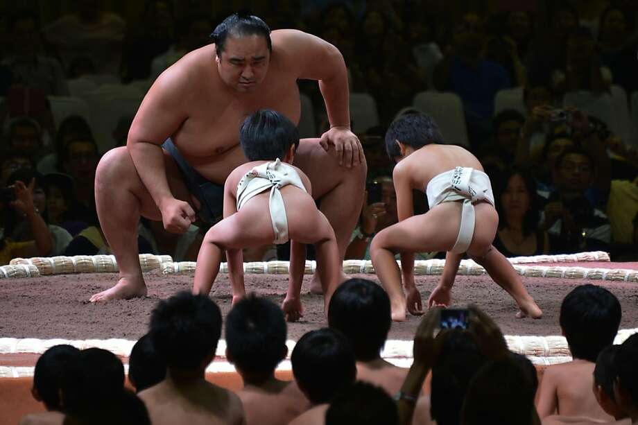 We are so dead:A Japanese sumo teacher takes on two neophytes in a mock wrestling match before a two-day sumo tournament in Jakarta, Indonesia. Photo: Bay Ismoyo, AFP/Getty Images