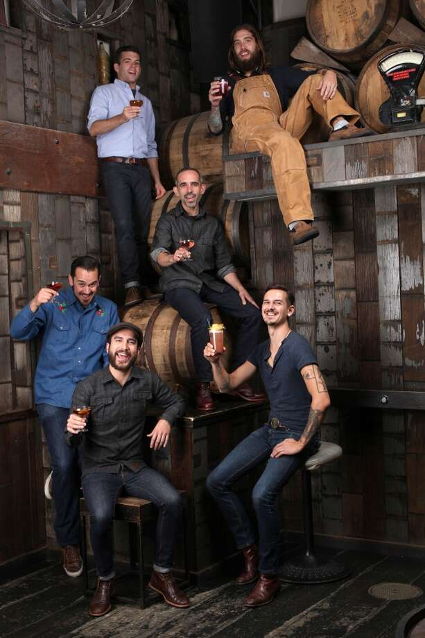 Clockwise from top left--Bartenders Michael Lay, Matthew Campbell (tan overalls), Chris Lane (lower right), Dan Stahl (seated left), Lucien Sankey, and Matty Conway (middle seated on barrel) photographed at Rickhouse in San Francisco. Photo: Liz Hafalia, The Chronicle