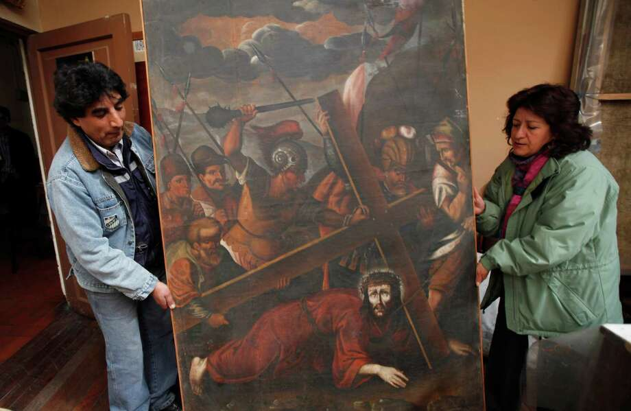 "In this Aug. 21, 2013 file photo, workers from the Culture Ministry display a recovered 18th century painting by an anonymous artist depicting Jesus in La Paz, Bolivia. This painting titled ""Jesus con la Cruz a Cuesta"" was stolen from the San Pedro de la Paz church in Bolivia on June 11, 2003, and recovered in the Peruvian capital of Lima in April 2005.  Increasingly bold thefts plague colonial churches in remote Andean towns in Bolivia and Peru, where religious and civil authorities say cultural treasures are disappearing at an alarming rate.  (AP Photo/Juan Karita) ORG XMIT: XJK301 Photo: Juan Karita / AP"