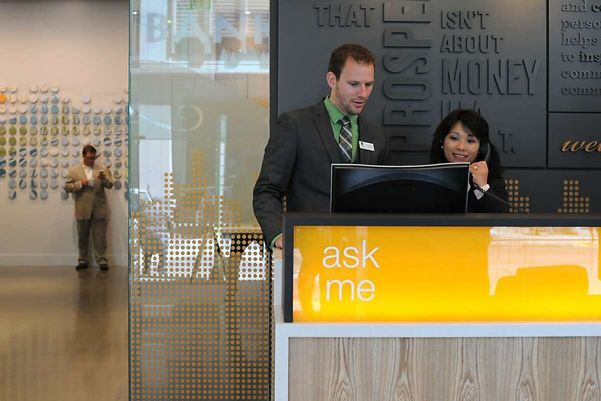 Universal Assistant Josh Farenbaugh and VP Store Manager Mary Wong are seen at the concierge's desk to greet guests at Umpqua Bank's flagship store in San Francisco, California on Monday, August 26, 2013.