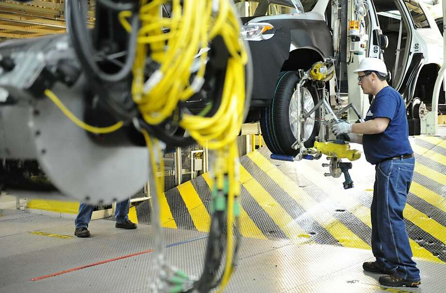 David Hurt attaches tires to a 2012 Toyota Highlander vehicles at the Toyota Motor Manufacturing Indiana, Inc., plant in Princeton, Ind., on Wednesday, Feb. 8, 2012. Toyota says it will expand its factory in Princeton, Indiana, and add 400 jobs so it can build more Highlander SUVs. Photo: Erin McCracken, Associated Press