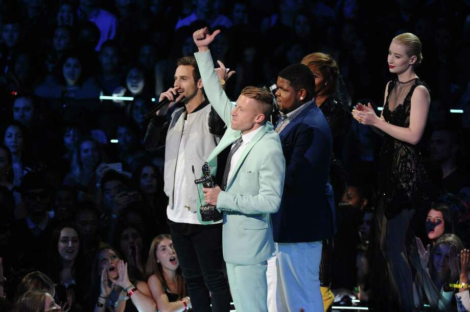 "Ryan Lewis, left, Macklemore, center, and Ray Dalton accept the award for best hip hop video for ""Can't Hold Us"" as presenters Iggy Azalea, right, and Lil' Kim look on, at the MTV Video Music Awards on Sunday, Aug. 25, 2013, at the Barclays Center in the Brooklyn borough of New York. (Photo by Charles Sykes/Invision/AP) Photo: AP"