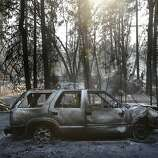 A burned-out SUV sits within the swath of destruction wrought by the Rim Fire, which had burned 235 square miles by Monday.