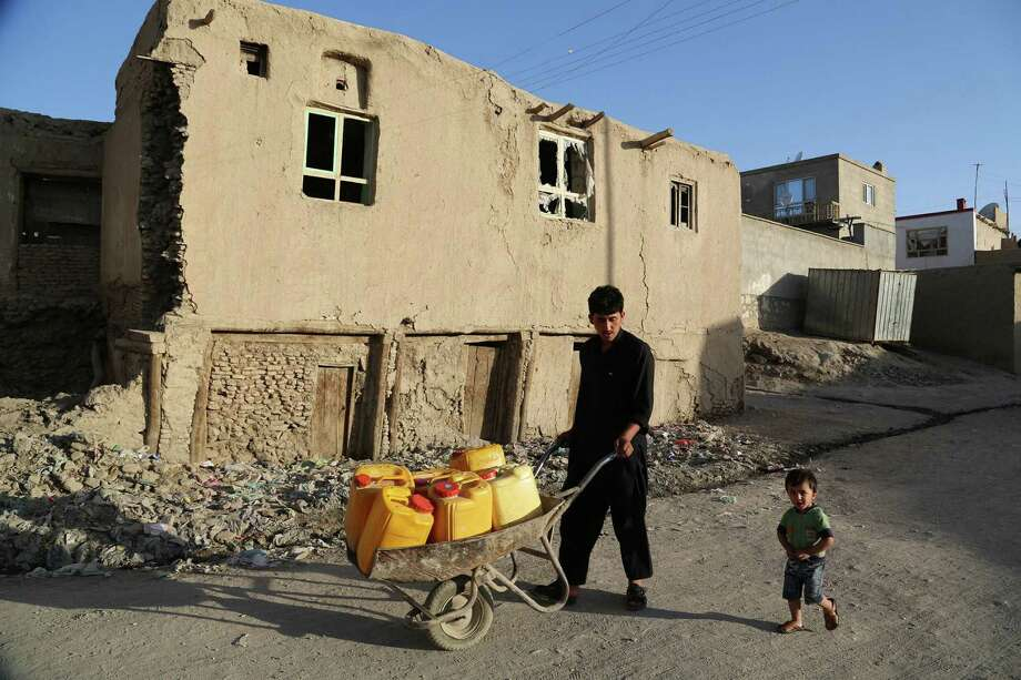 An Afghan resident hauls water in Ghazni on Sunday. Decades of conflict have left Afghanistan's economy in tatters, and the country is heavily dependent on foreign aid. Photo: Rahmatullah Alizada / Getty Images