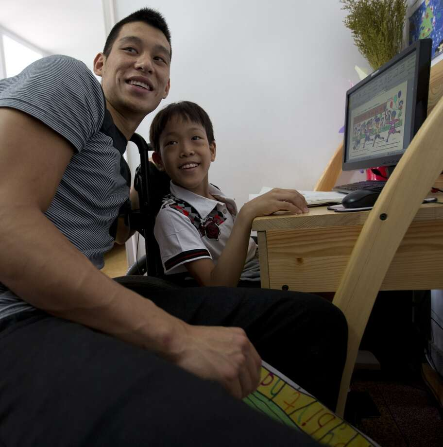 Jeremy Lin poses for photos with a child during his visit at an orphanage and rehabilitation center that serves children with congenital illnesses such as cerebral palsy in Tianjin, China, on Saturday. Photo: Alexander F. Yuan, Associated Press