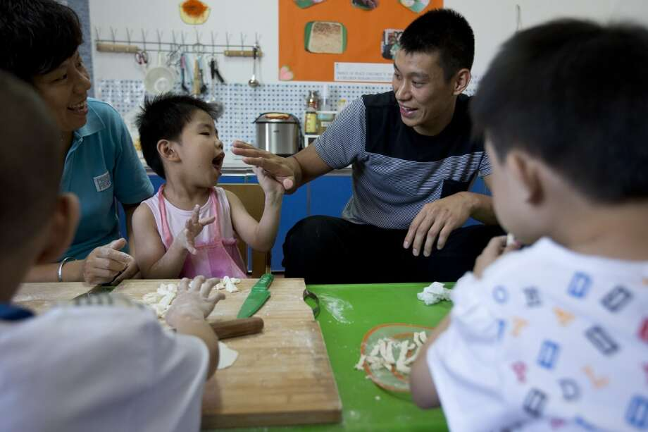 Jeremy Lin plays with children during his visit to an orphanage and rehabilitation center in Tianjin, China. Photo: Alexander F. Yuan, Associated Press