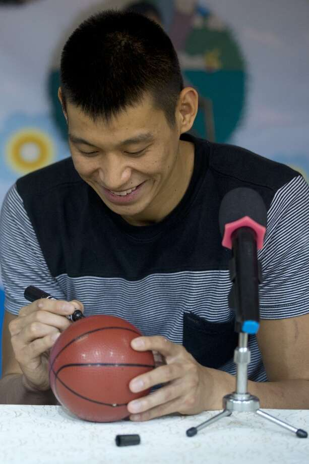 Jeremy Lin autographs a ball during his visit to an orphanage and rehabilitation center in Tianjin, China Photo: Alexander F. Yuan, Associated Press