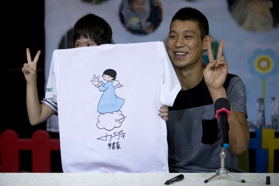 Jeremy Lin poses for photos with a child after he signed his name on a T-shirt. Photo: Alexander F. Yuan, Associated Press
