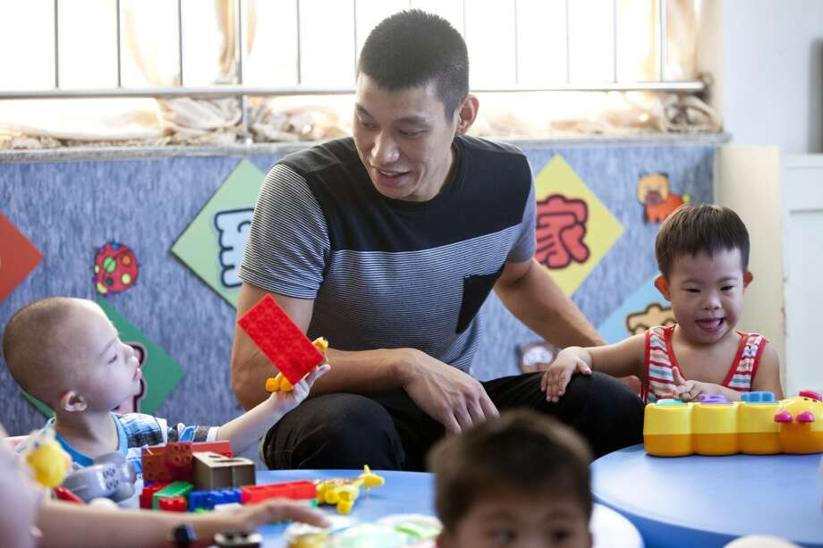 Jeremy Lin plays with children during his visit at an orphanage and rehabilitation center that serves children with congenital illnesses such as cerebral palsy in Tianjin, China. Photo: Alexander F. Yuan, Associated Press