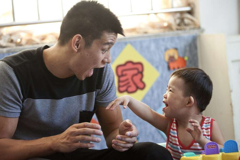 Jeremy Lin makes a funny face to draw a smile from a young child. Photo: Alexander F. Yuan, Associated Press