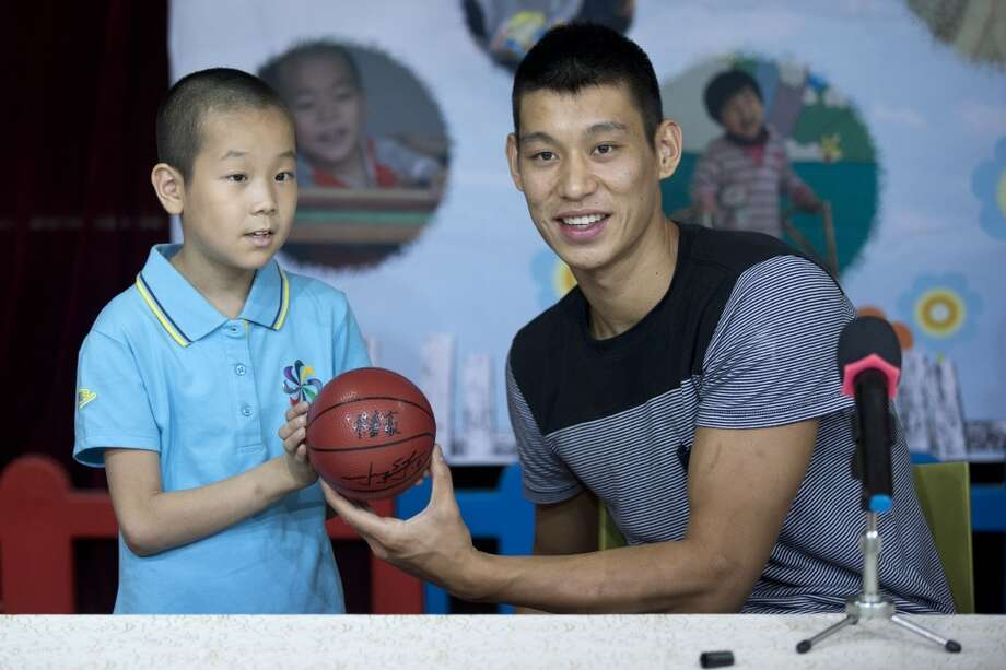 Jeremy Lin poses for a photo with a child. Photo: Alexander F. Yuan, Associated Press