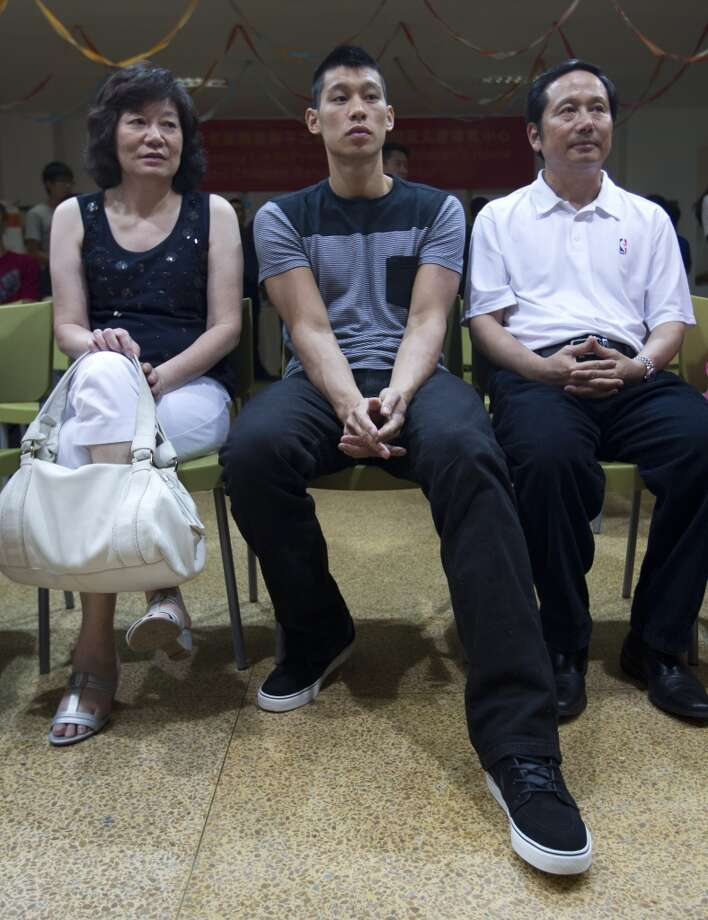 Jeremy Lin, center, his mother Shirley Lin, left, and his father Gie-ming Lin, right, take their seats during their visit to an orphanage and rehabilitation center in Tianjin, China. Photo: Alexander F. Yuan, Associated Press