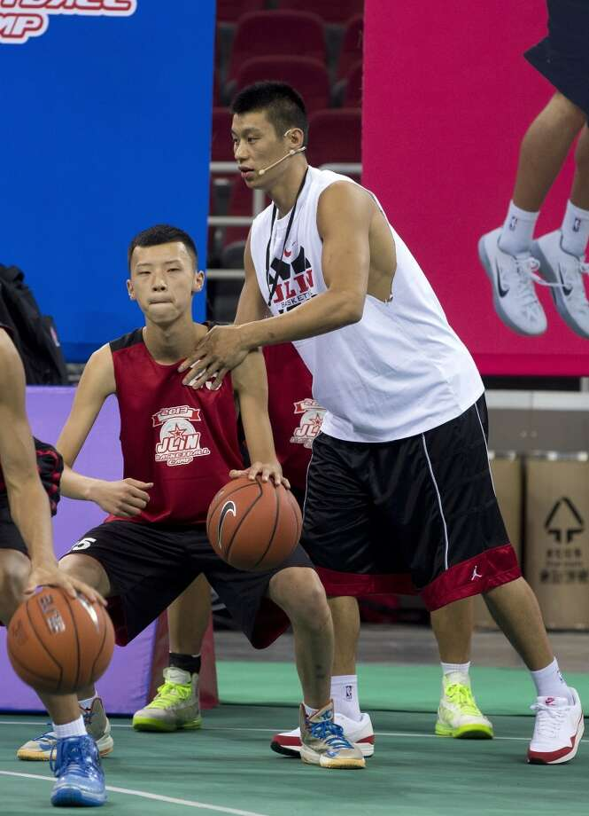 Jeremy Lin, right, gives instruction during a basketball camp in Beijing, China on Sunday. Photo: Andy Wong, Associated Press