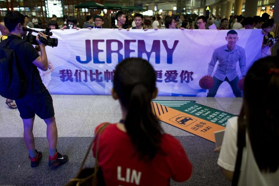 Fans hold a banner featuring Jeremy Lin while they wait for his arrival at the Beijing International Airport on Friday. Photo: Alexander F. Yuan, Associated Press