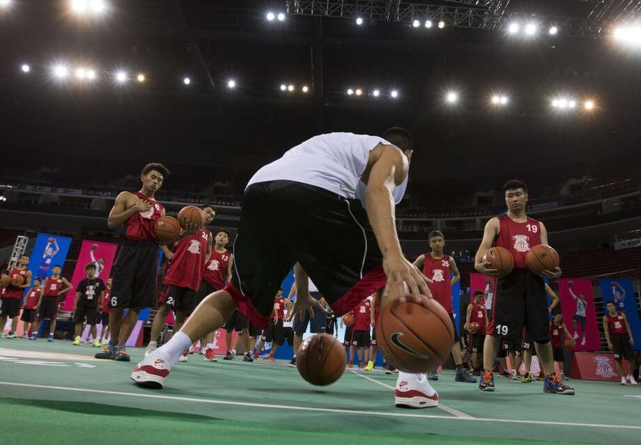 Jeremy Lin, center, shows his skills to young players during a basketball camp. Photo: Andy Wong, Associated Press