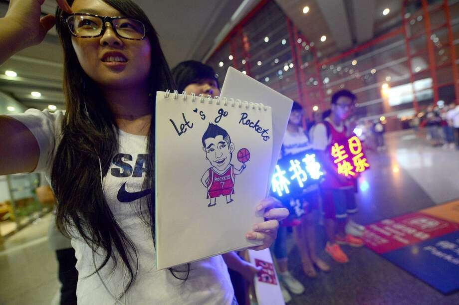 A fan holds a cartoon of Jeremy Lin as she waits for his arrival at an airport in Beijing on Friday. Photo: Wang Zhaowang Zhao, Getty Images