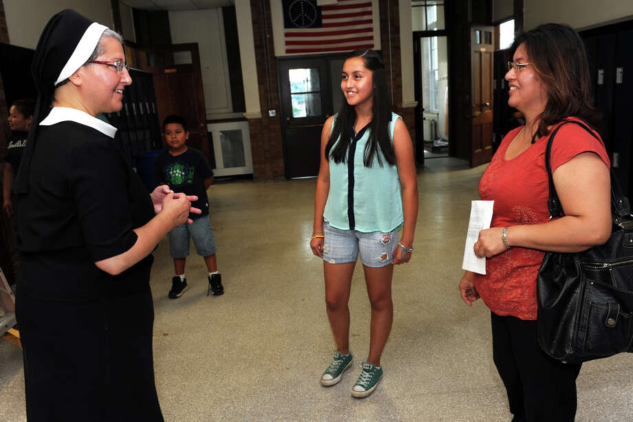 Teacher Sister Lisa Florio welcomes 8th grader Mayra Vargas and her mother Sara Pineda to the new Cathedral Academy Intermediate & Middle School Campus during an open house in Bridgeport, Conn., Aug. 26, 2013. Photo: Ned Gerard / Connecticut Post