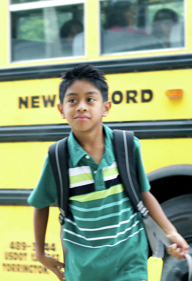 Second-grader Matty Napoli strides from his school bus with confidence as he and his fellow John Pettibone School School students start the 2013-14 school year in New Milford. Photo: Trish Haldin