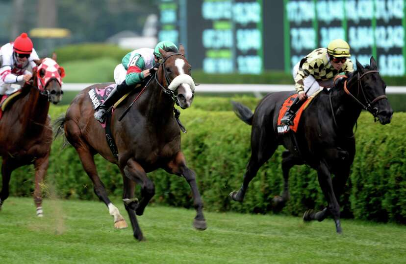Madame Giry with jockey Joseph Rocco Jr., left,  passes #7 Rosa Salvaje with jockey Alex Solis to wi