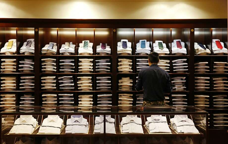 Brooks Brothers visual coordinator Brian Chan works among a display of shirts. Photo: Lea Suzuki, The Chronicle