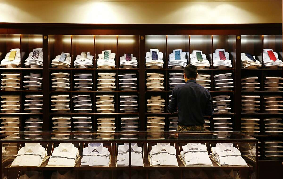 Brooks Brothers visual coordinator Brian Chan works among a display of shirts at the new Brooks Brother store on Thursday, August 22, 2013 in San Francisco, Calif.