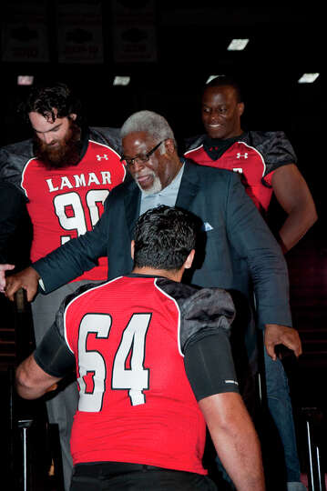 Earl Campbell (center) escorted off the stage by Mark Murrill (90) Jesse Dickson (93) and Kyle Gilla