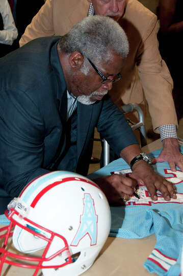 Earl Campbell signing a Houston Oilers jersey for the winning bidder of an Earl Campbell jersey and