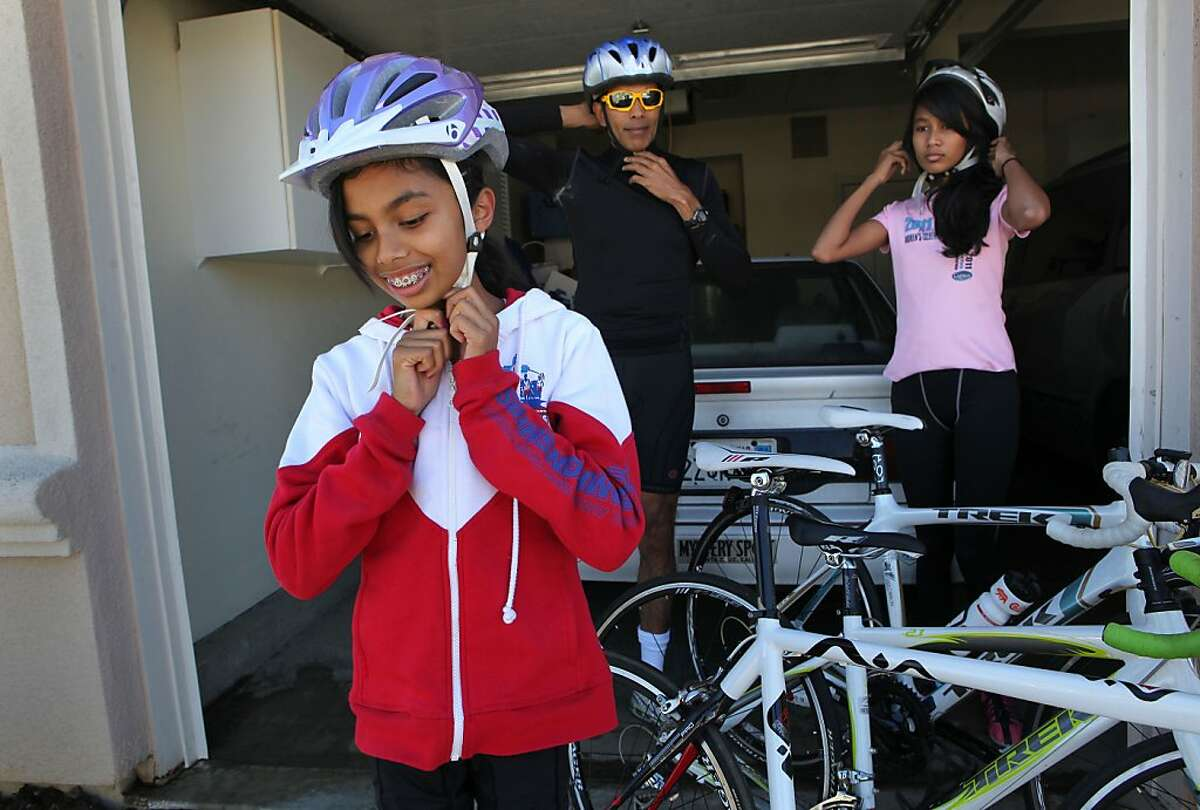 11-year-old Rithika Vatturi with her father Arun and sister Priyanka, in Union City, Calif. on Saturday August 24, 2013. Rithika, getting ready for a bike ride, is able to train for the triathlons she participate in without the use of glasses. Doctors and researchers are developing new techniques to slow down or even prevent the progression of myopia (nearsightedness) once it starts in kids. Once such technique uses hard contact lens known as