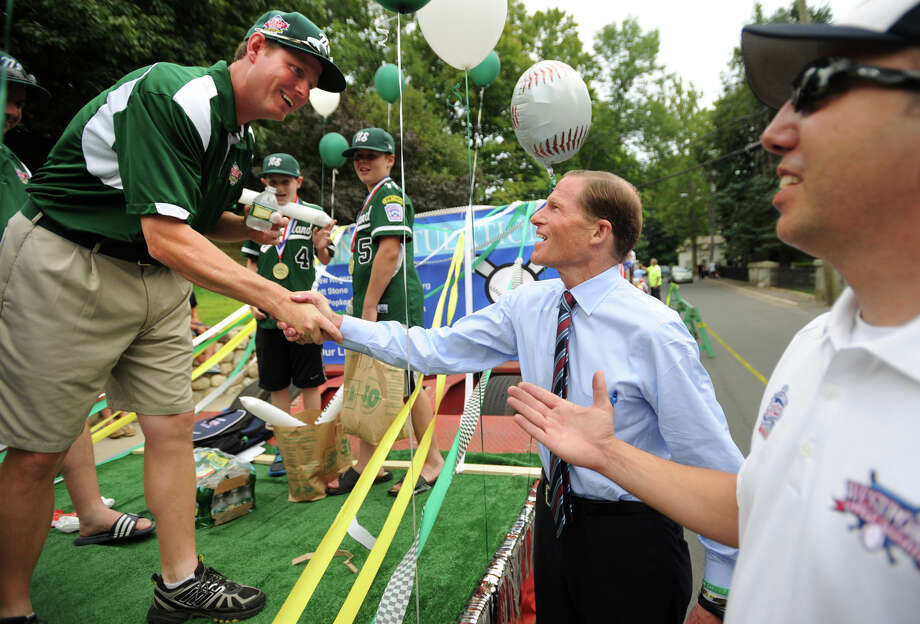 Westport Little League head coach Tim Rogers, left, shakes hands with U.S. Senator Richard Blumenthal before the start of a parade honoring the Little League boys baseball and girls softball champions in downtown Westport, Conn. on Monday, August 26, 2013. Photo: Brian A. Pounds / Connecticut Post