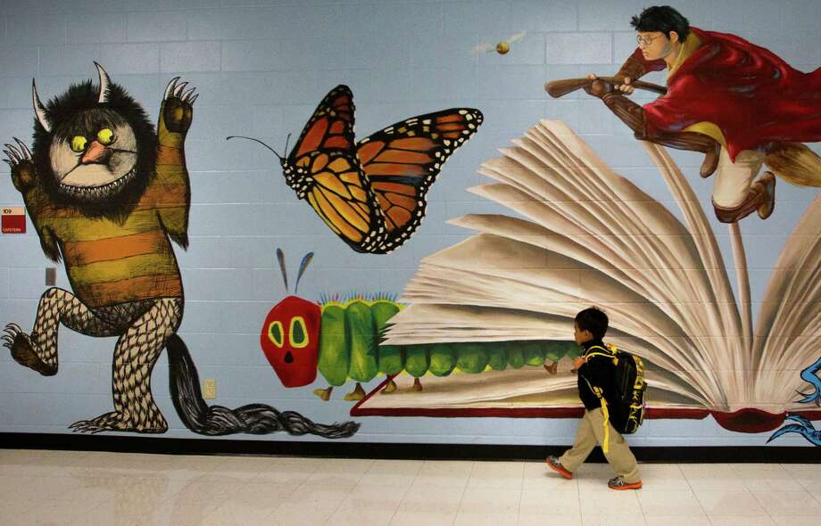 Caleb Fernandez, 4, walks past a new mural Monday on his way to join classmates at Thurgood Marshall Elementary. Photo: Cody Duty, Staff / © 2013 Houston Chronicle