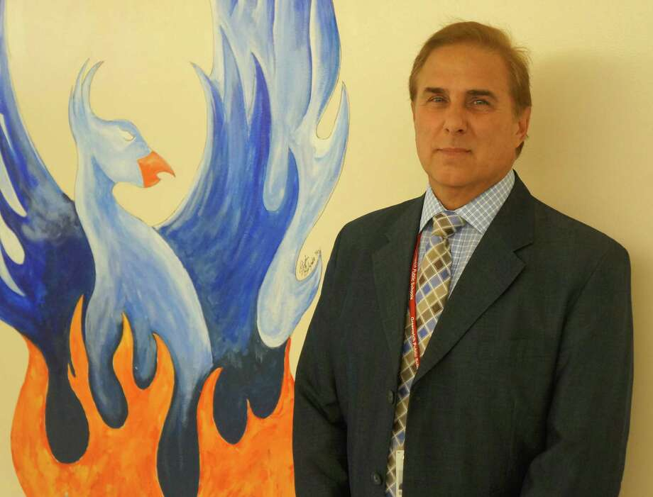 Gene Schmidt, Cos Cob School s new principal, stands in the hallway next to a painting of a phoenix, which is the school s mascot. Photo: Greenwich Time