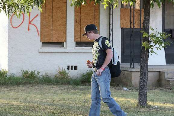 A student heading to school on Monday walks past one of the homes that were boarded up because of the plant explosion.