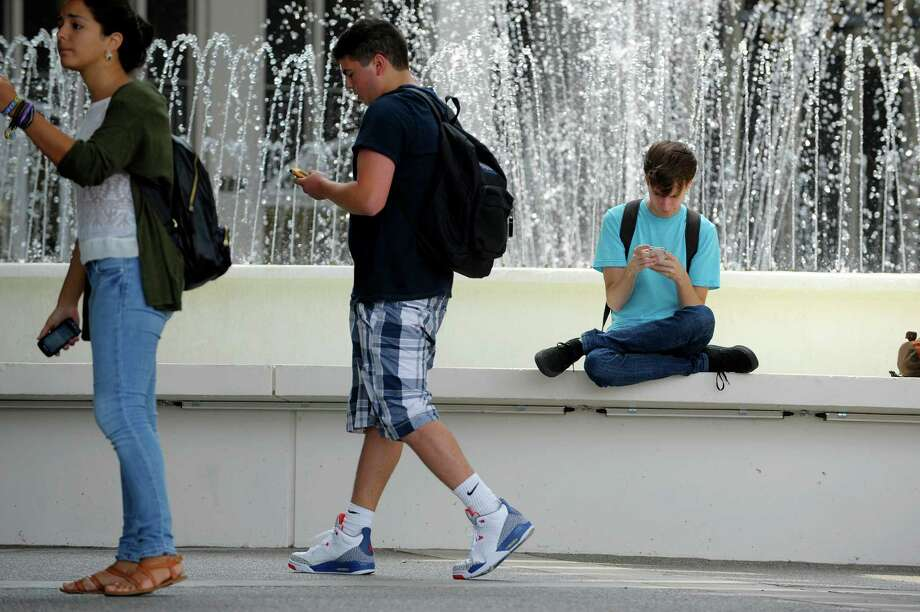 UAlbany senior, Evan West, right, from Albany uses his smart phone outside the Campus Center between classes at the UAlbany campus on Monday, Aug. 26, 2013 in Albany, N.Y. (Paul Buckowski / Times Union) Photo: Paul Buckowski / 00023644A