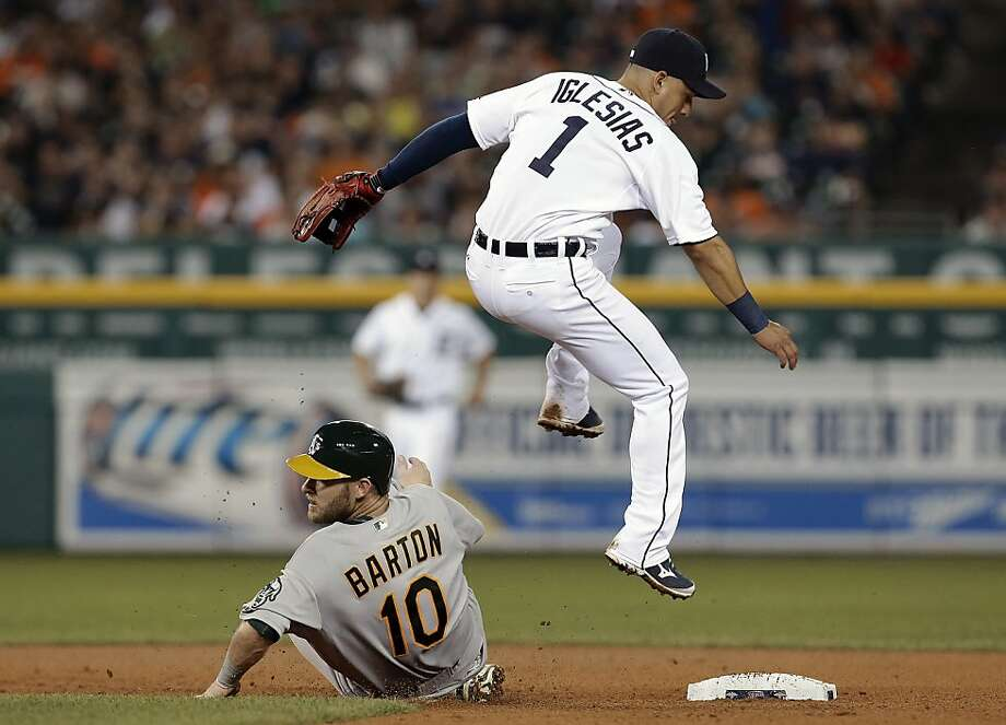 Detroit shortstop Jose Iglesias leaps to avoid the sliding Daric Barton. Photo: Paul Sancya, Associated Press