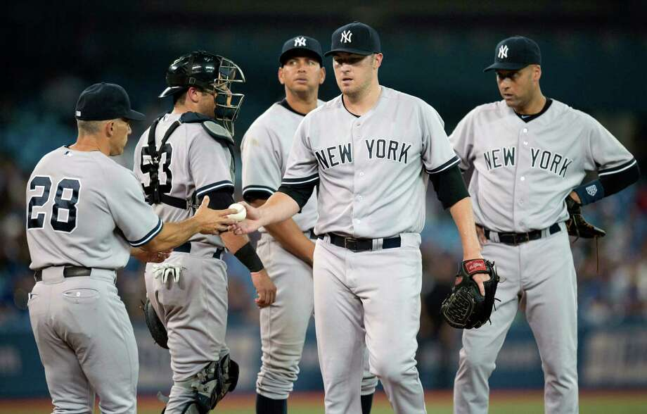 New York Yankees catcher Austin Romine, rear left to right, third baseman Alex Rodriguez and shortstop Derek Jeter watch as starting pitcher Phil Hughes is pulled from the game by manager Joe Girardi (28) during the fifth inning of a baseball game against the Toronto Blue Jays in Toronto on Monday, Aug. 26, 2013. (AP Photo/The Canadian Press, Frank Gunn) ORG XMIT: FNG218 Photo: Frank Gunn / The Canadian Press