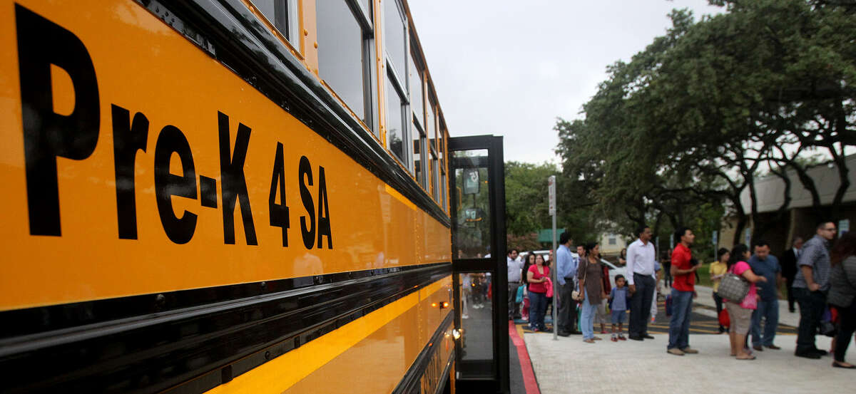 Parents and children line up by a bus in front of the Pre-K 4 SA North Center in the Medical Center on the first day of school. The initiative will provide full-day pre-K education for an estimated 22,400 4-year-olds over eight years.