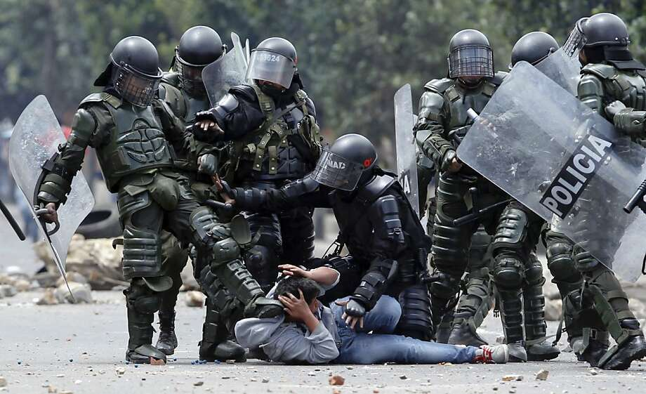 A riot police officer, left, kicks a protester as another, center, tries to protect him before his arrest during protests in Ubate, north of Bogota, Colombia, Monday, Aug. 26, 2013.  Hundreds of protesters clashed with police in support of farmers who have being blockading Colombian highways for a week for an assortment of demands that include reduced gasoline prices, increased subsidies and the cancellation of free trade agreements. (AP Photo/Fernando Vergara) Photo: Fernando Vergara, Associated Press
