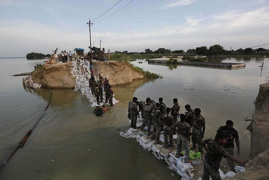 Indian army soldiers work to repair an embankment that was washed away due to heavy flooding of the Ganges river in Allahabad, India, Monday, Aug. 26, 2013. India's monsoon season, which runs from June through September, brings rains that are vital to agriculture but also cause floods and landslides. (AP Photo/Rajesh Kumar Singh) Photo: Rajesh Kumar Singh, Associated Press
