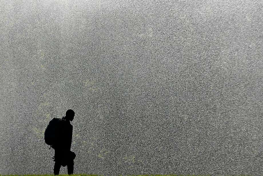 A man refreshes  in front of a sprinkler in the Tiergarten park in Berlin, Monday, Aug. 26, 2013. Weather forecasts predict changeable weather for Germany.  (AP Photo/Markus Schreiber) Photo: Markus Schreiber, Associated Press