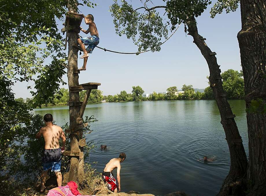 Swimmers use a rope swing over Airport Lake on Monday, Aug. 26, 2013, in Winona, Minn. Temperatures on Monday are forecast to approach a record 98 in the Twin Cities, but the humidity will make it feel like 100 to 110 across much of southern Minnesota. An excessive heat warning remains in effect for the region through Tuesday. (AP Photo/Winona Daily News, Andrew Link) Photo: Andrew Link, Associated Press