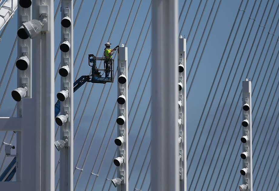 SAN FRANCISCO, CA - AUGUST 26:  A worker makes adjustements to a light pole sign on the new eastern span of the Bay Bridge on August 26, 2013 in San Francisco, California. After nearly 12 years of construction and an estimated price tag of $6.4 billion, the new eastern span of the Bay Bridge is set to open on September 3. The bridge will be the world's tallest Self-Anchored Suspension (SAS) tower once completed.  (Photo by Justin Sullivan/Getty Images) Photo: Justin Sullivan, Getty Images
