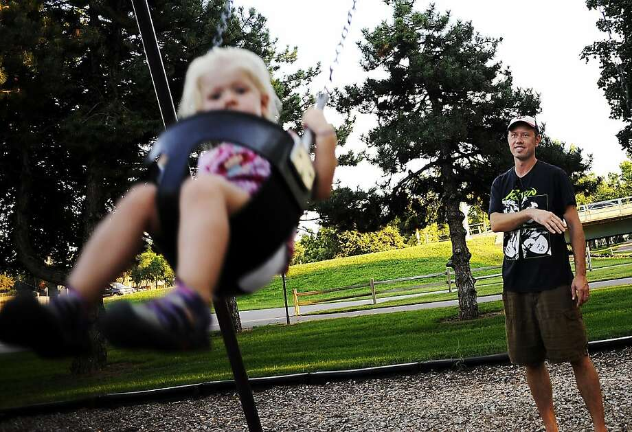 Tim Haugrud pushes his 2-year-old daughter Ruby Haugrud on the swing at Rotary-Norlin Park in Sioux Falls, S.D., on Monday, Aug. 26, 2013. Haugrud said they picked Rotary-Norlin Park because it had the most trees, which meant there would be more shade to escape Monday's heat. (AP Photo/Argus Leader, Joe Ahlquist) Photo: Joe Ahlquist, Associated Press
