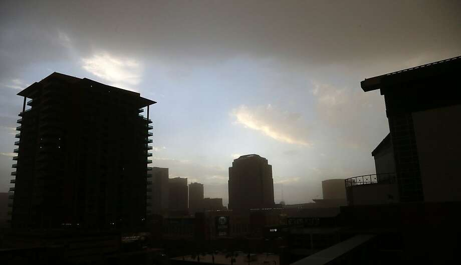 A dust storm blocks out the sun as it moves through downtown Phoenix on Monday, Aug. 26, 2013. (AP Photo/Ross D. Franklin) Photo: Ross D. Franklin, Associated Press