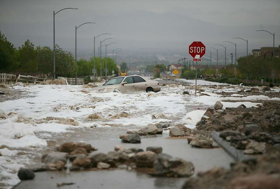 An abandoned and stalled car is engulfed in flood waters rushing through the intersection of Grand Teton Dr. and Grand Canyon Dr. in northwest Las Vegas, Monday, Aug. 26, 2013, in Las Vegas. Motorists took detours Monday around roads closed by debris and torrential runoff from thunderstorms spawned by the remnants of a tropical storm that also forced the rescue of people stuck in stalled vehicles. (AP Photo/Las Vegas Review-Journal, Ronda Churchill) LOCAL TV OUT; LOCAL INTERNET OUT; LAS VEGAS SUN OUT Photo: Ronda Churchil, Associated Press