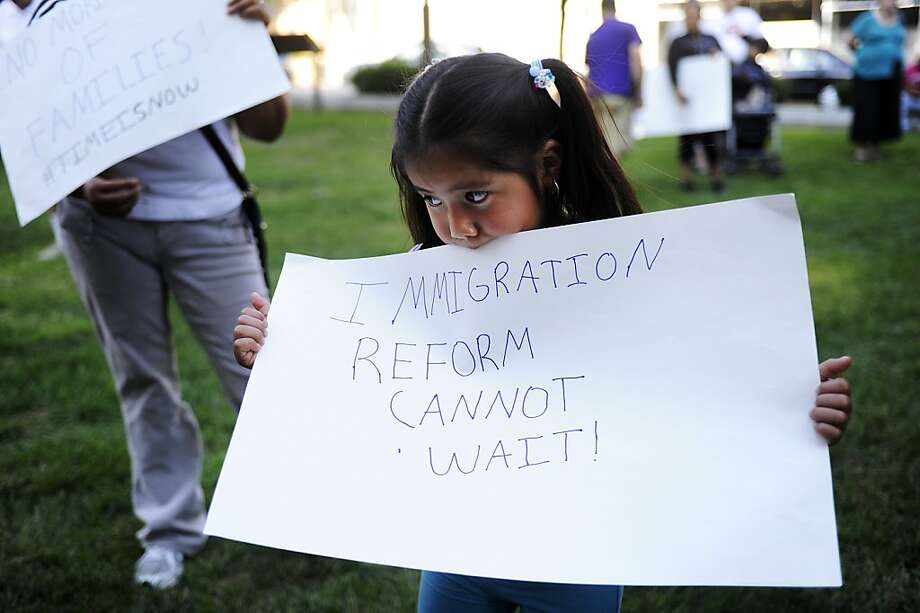 Jimena Avila, 3, holds up a sign before an immigration reform rally at Court Square on Monday, Aug. 26, 2013, in Harrisonburg. Rep. Luis Gutierrez (D-IL) spoke about comprehensive immigration reform, advocating a path to citizenship for immigrants. (AP Photo/The News Leader, Katie Currid) Photo: Katie Currid, Associated Press